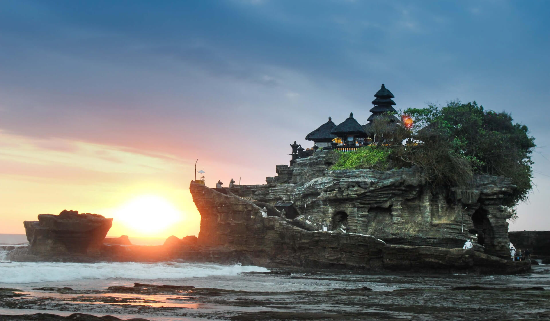 Balinese temple on a rock formation over the ocean with the sun setting behind it