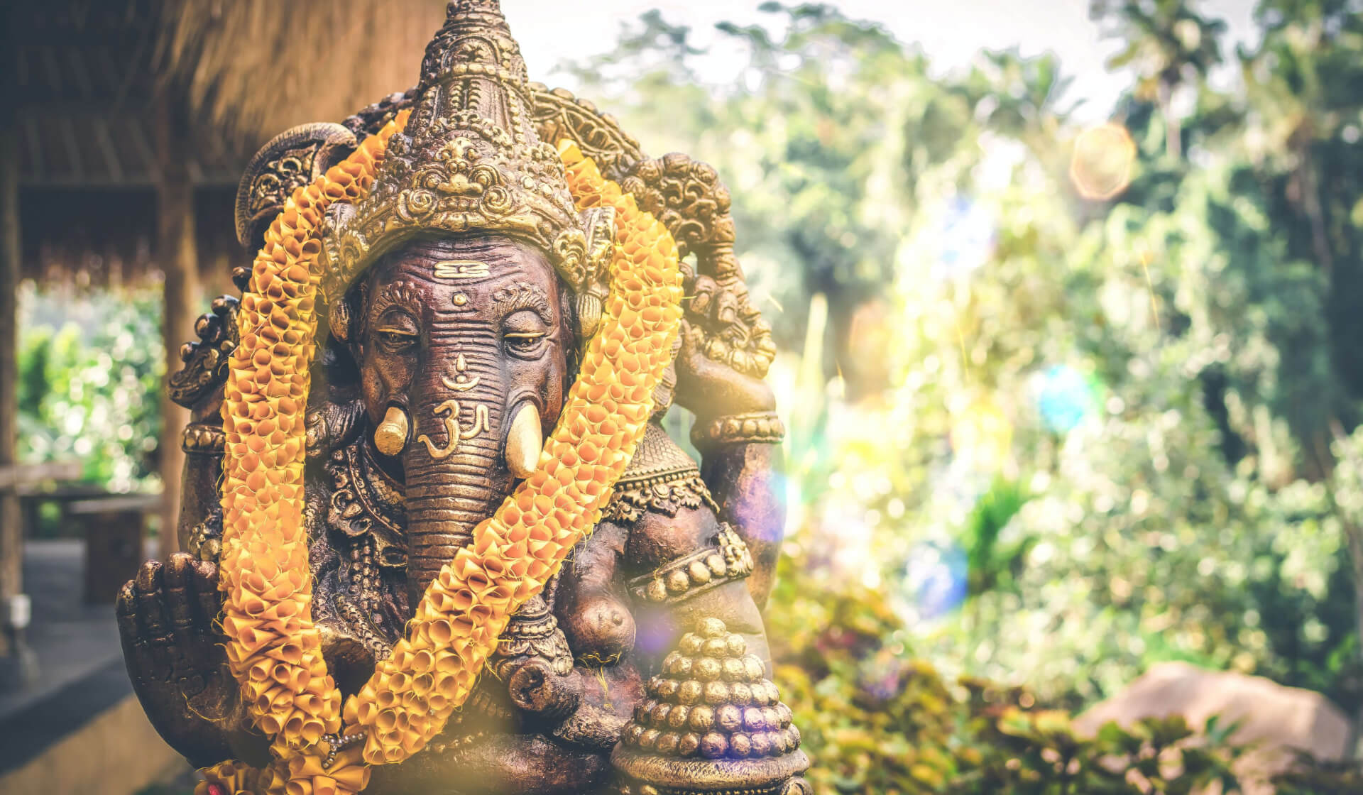 Balinese statue of Ganesha with an om symbol and yellow flowers around his neck with trees in the backgroundk