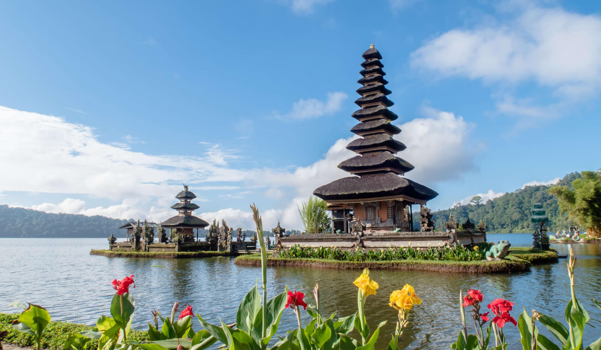 Balinese temples on a lake with colorful flowers and a blue sky