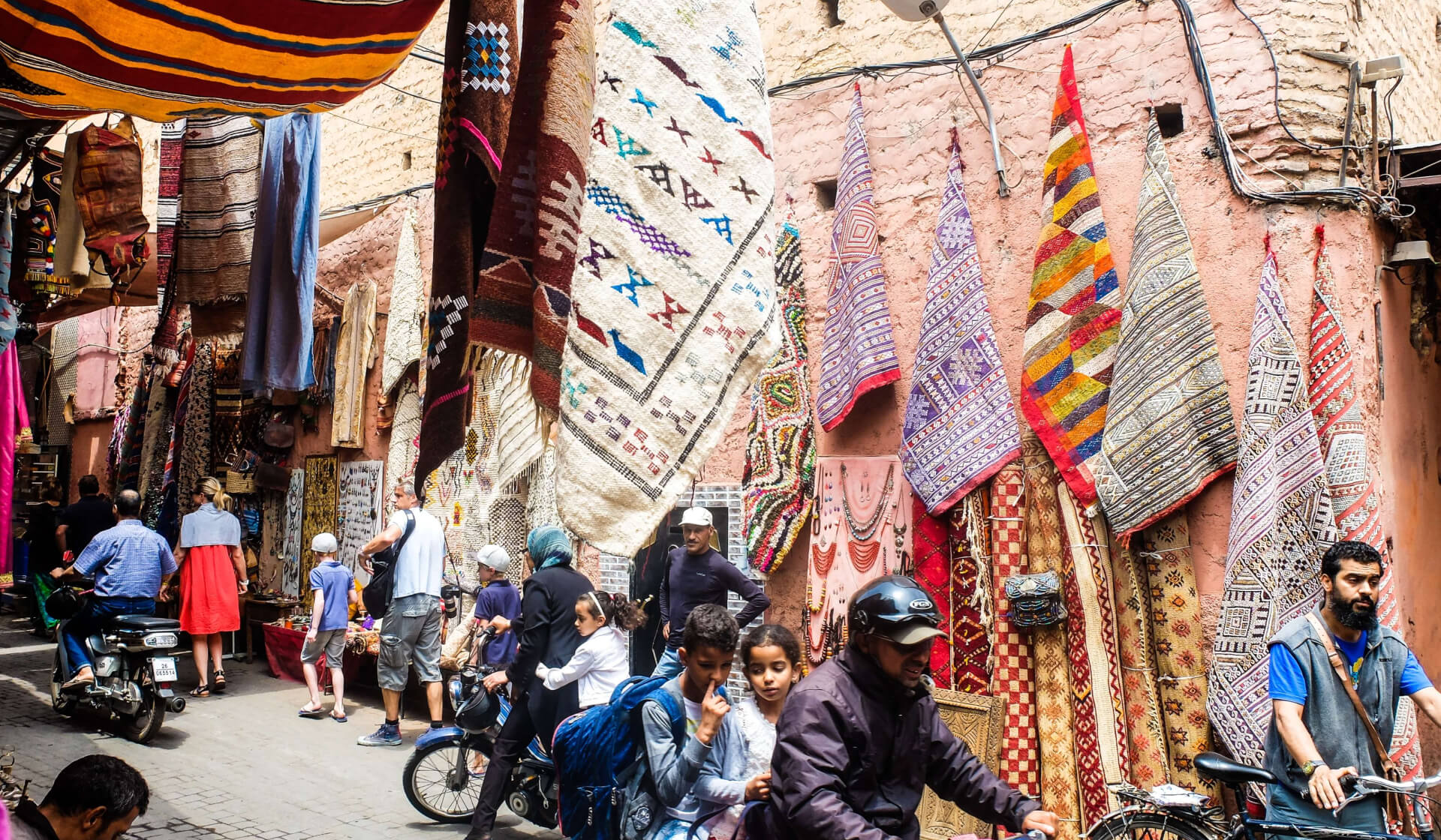 Souk in Marrakech, Morocco with colorful rugs on the walls and jewelry for sale and lots of people walking and a motorbike driving through a narrow street