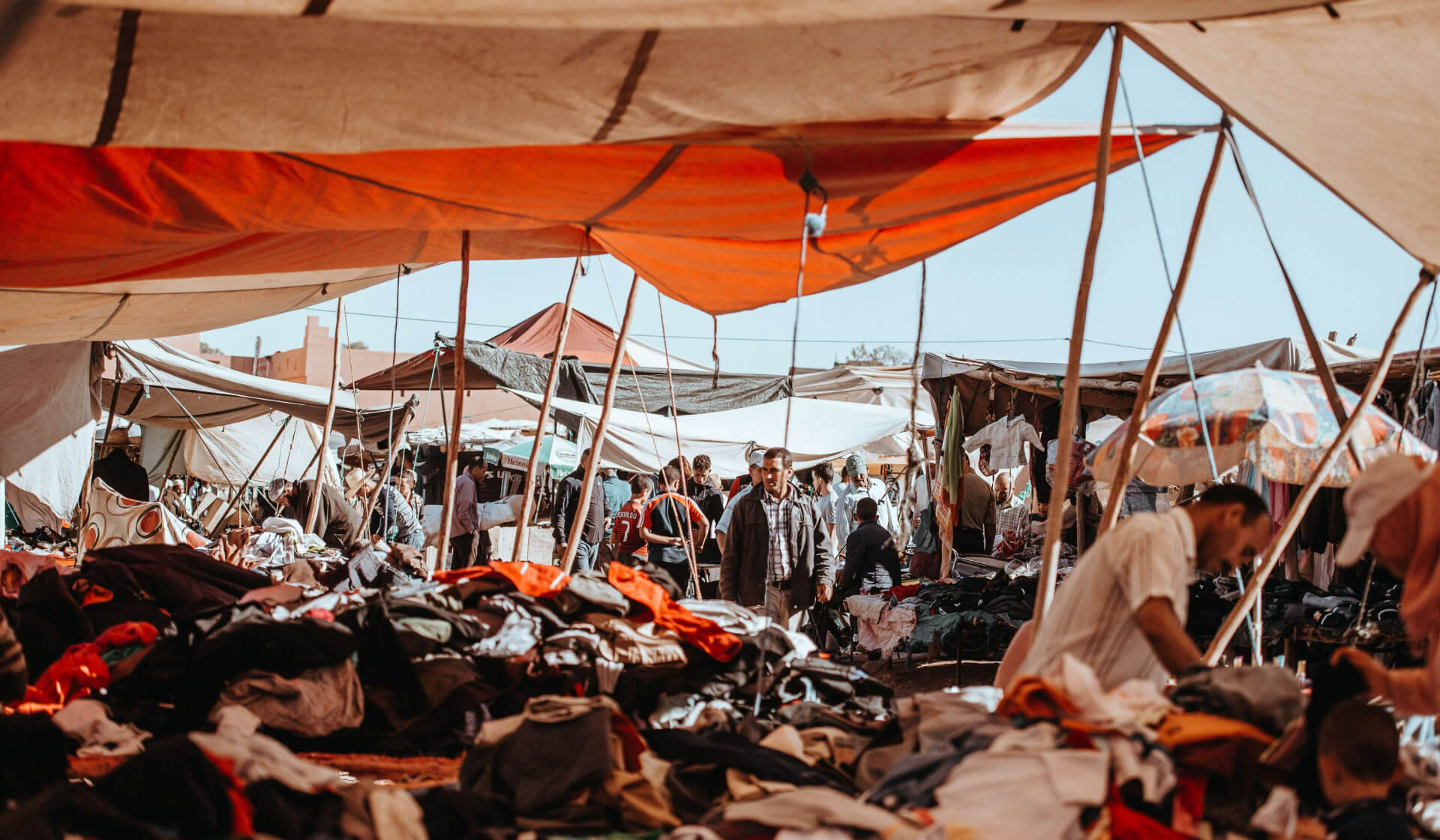 Busy souk market in Marrakech, Morocco with tent canopies and lots of clothing and people shopping