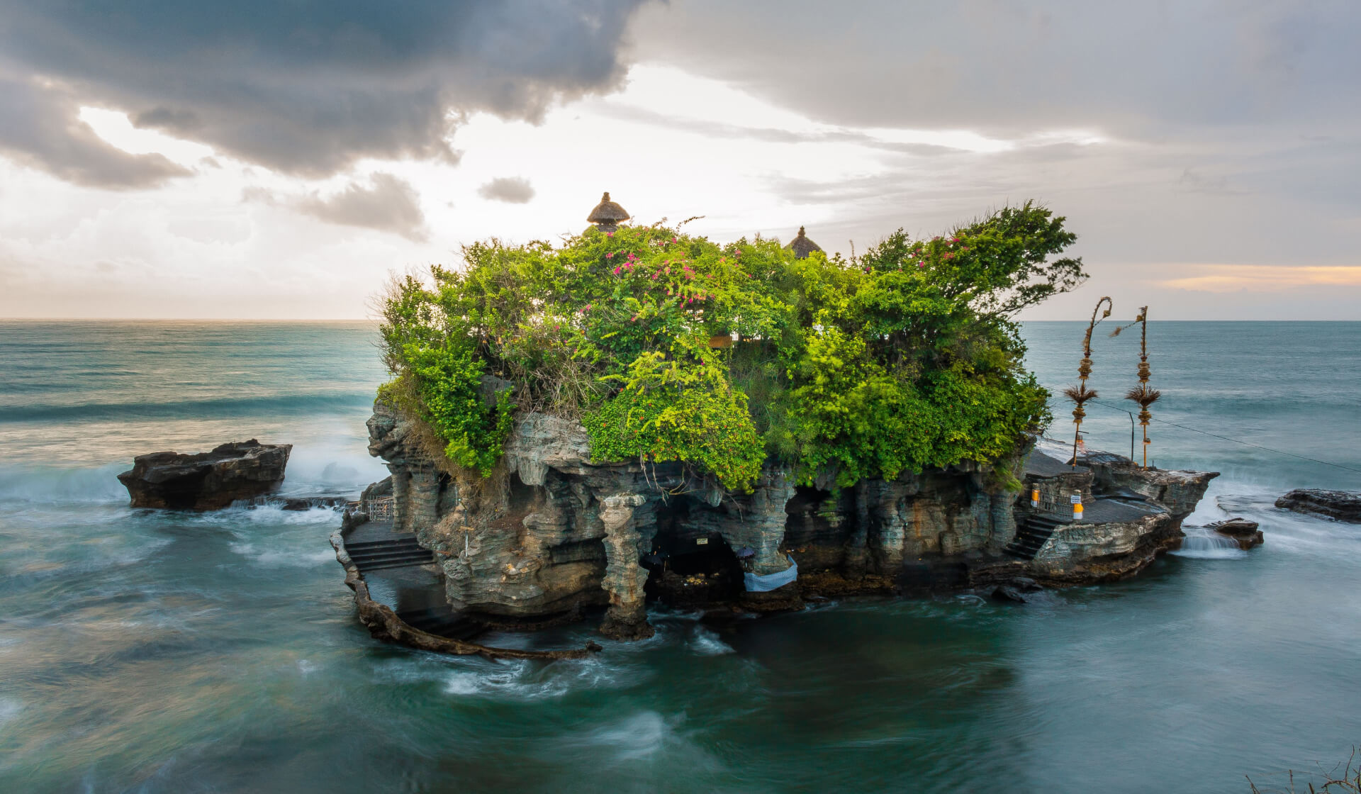 Balinese temple with lush green plants built on a rock formation overlooking the ocean