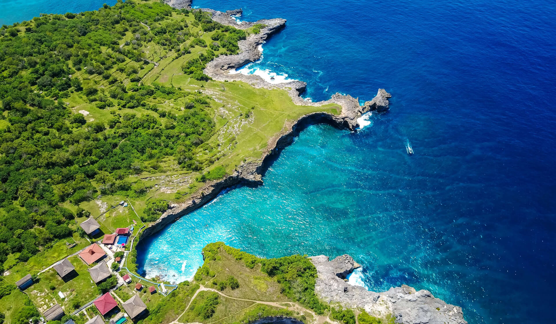 Aerial view of small green island (Nusa Ceningan) and crystal clear blue waters