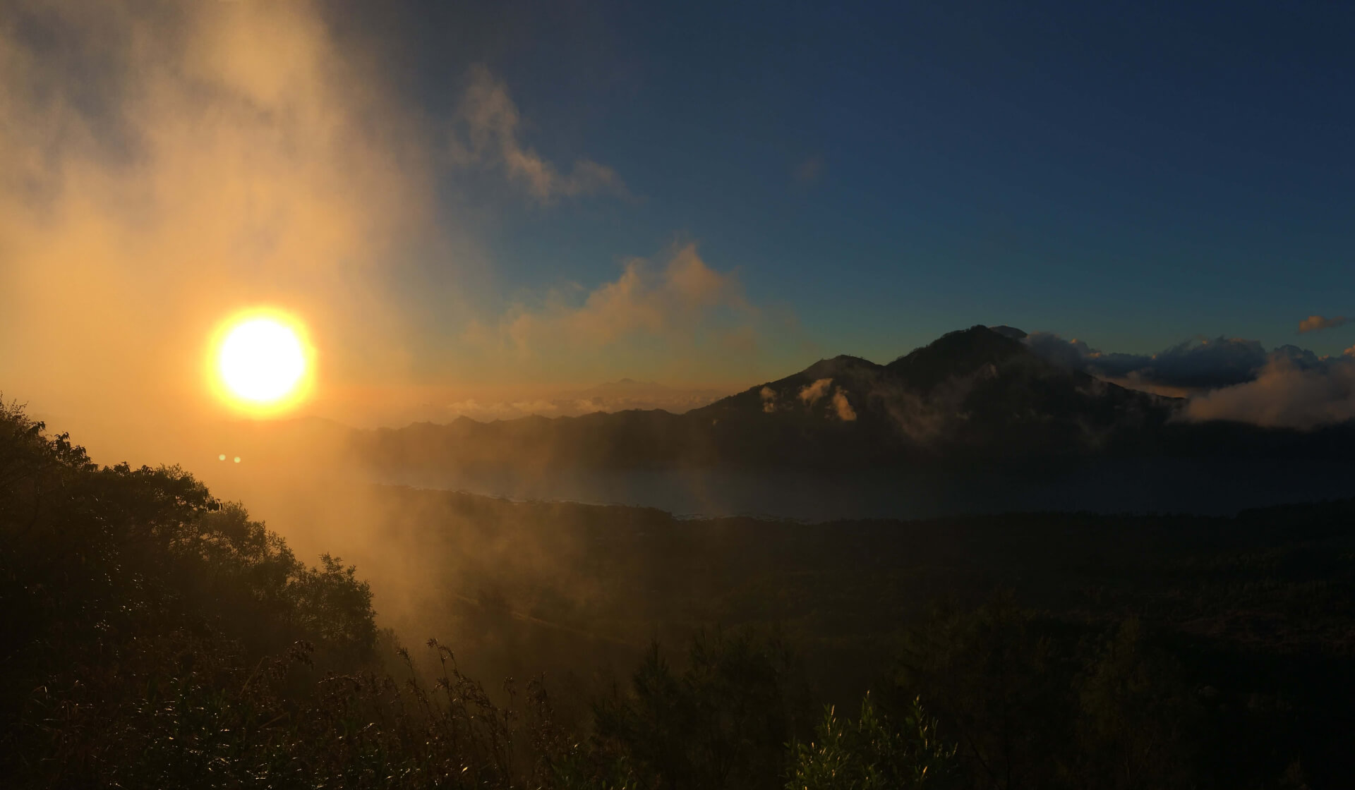 Misty sunrise over a huge lake and mountains from Mount Batur in Bali