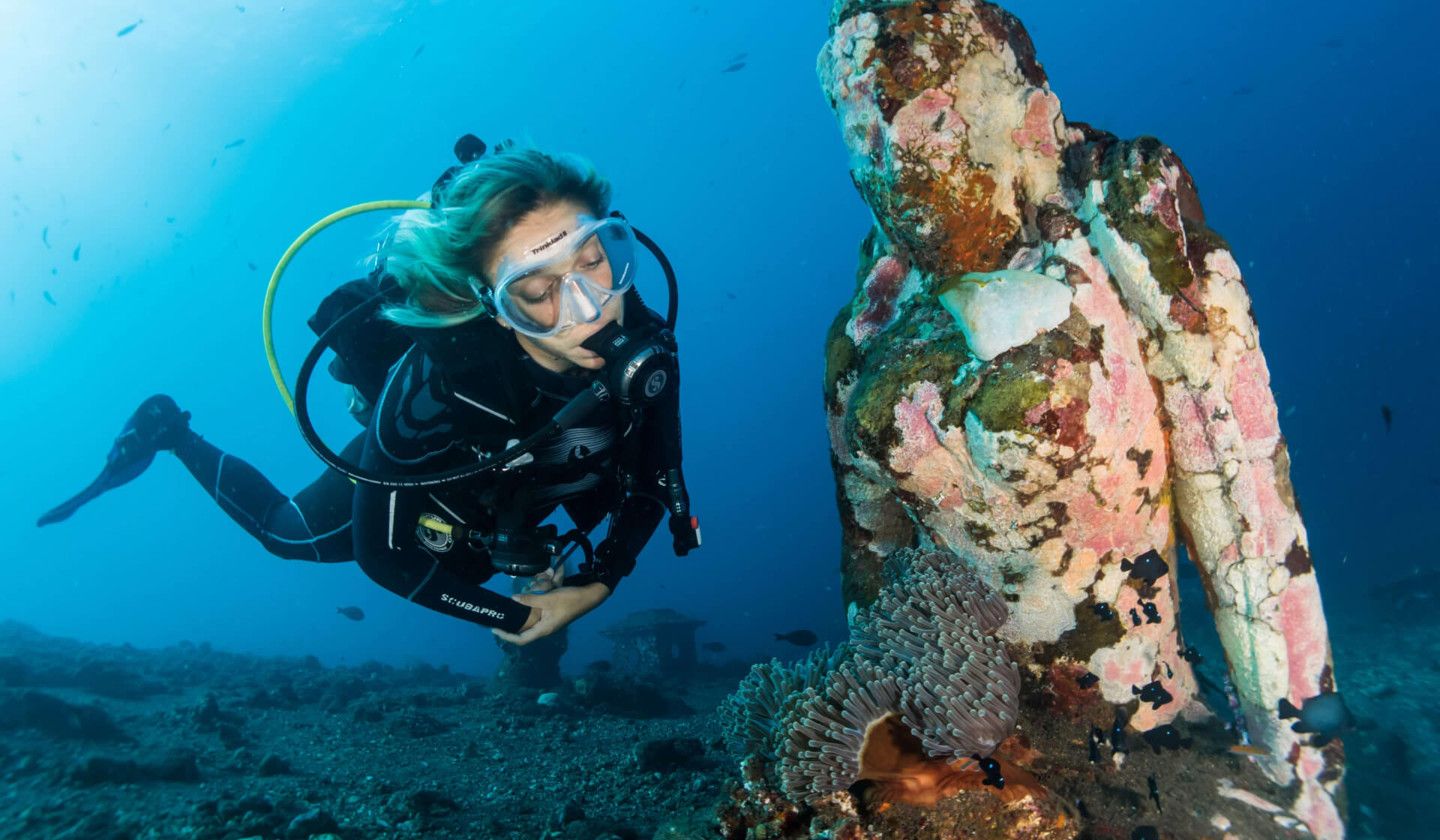 Women scuba diving next to an underwater statue covered in coral