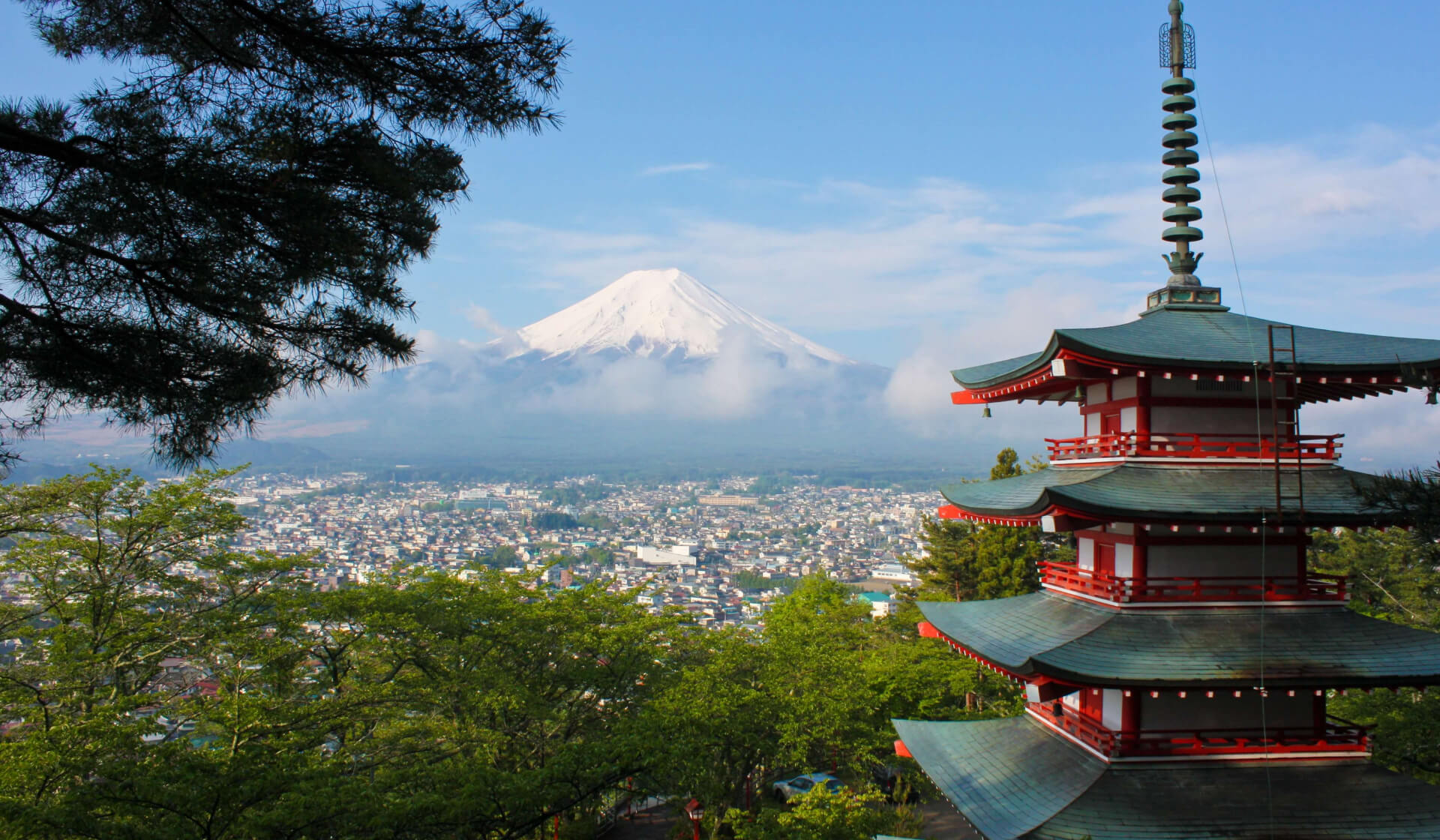Japanese temple overlooking a city landscape and enormous snow-capped mountain