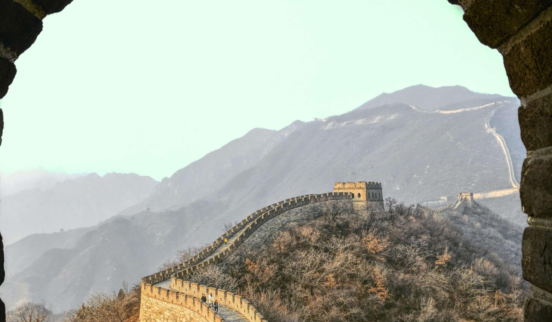 View through an open window of the Great Wall of China disappearing over the moutains