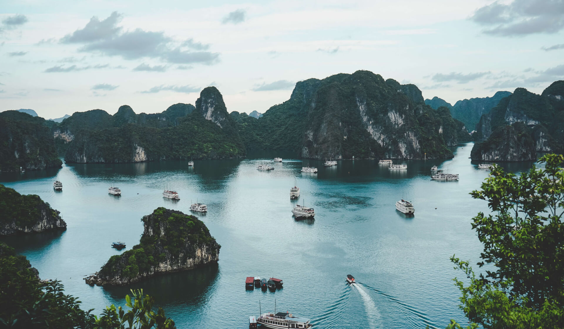 Aerial view of boats in blue water surrounded by green mountains in Halong Bay, Vietnam