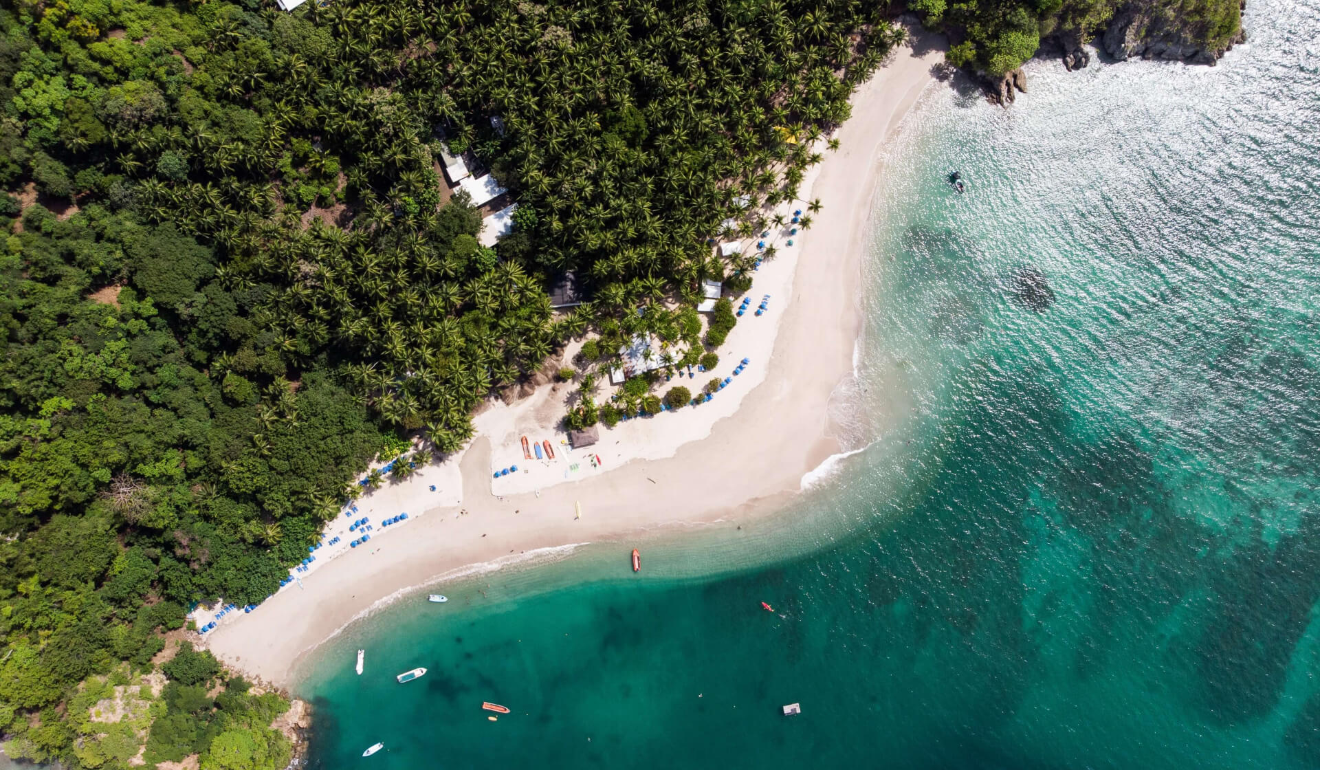 Aerial view of a white sand beach surrounded by palm trees and jungle and crystal clear blue water in Costa Rica