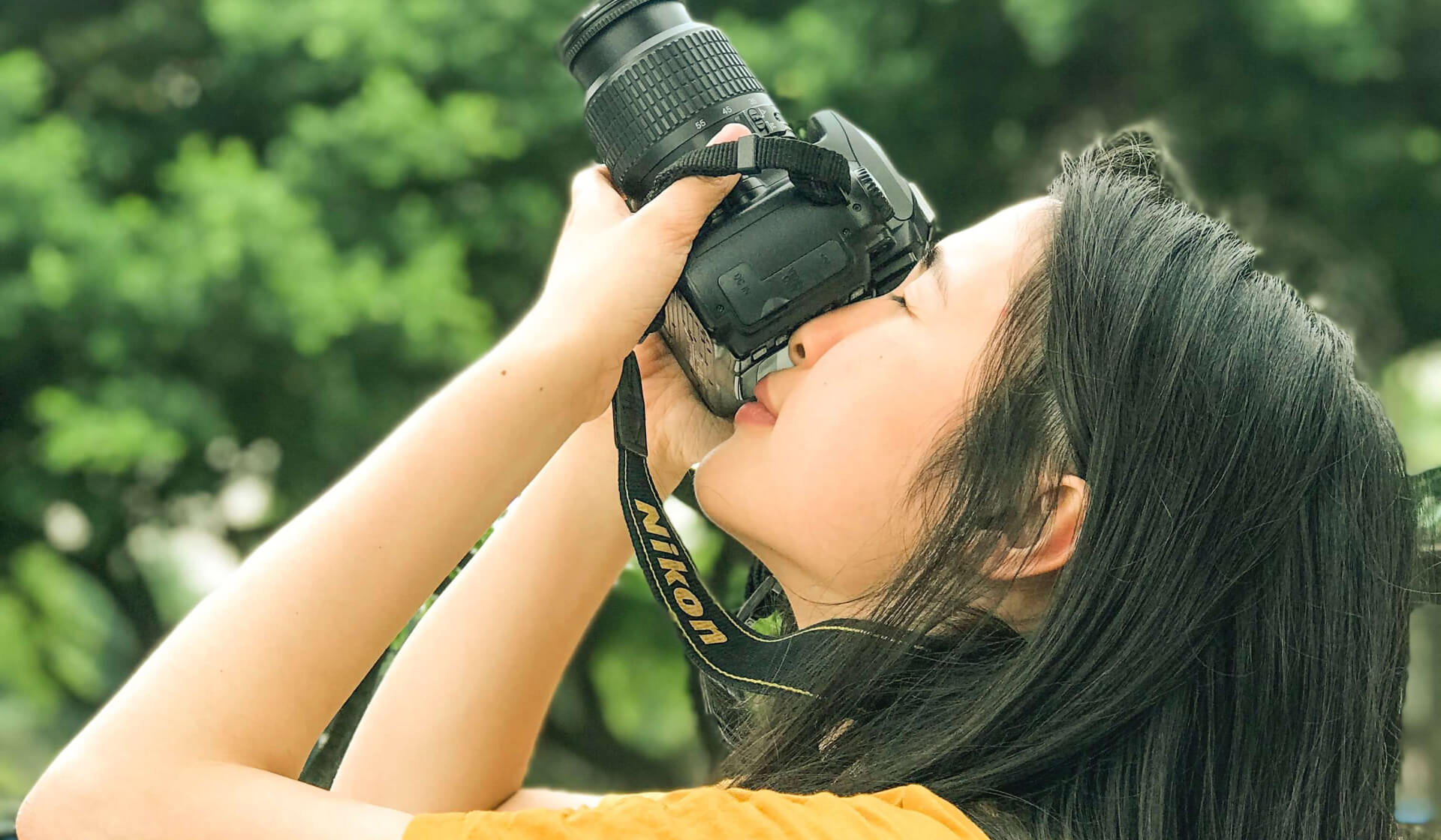 Woman looking into a camera and taking a photograph of something above