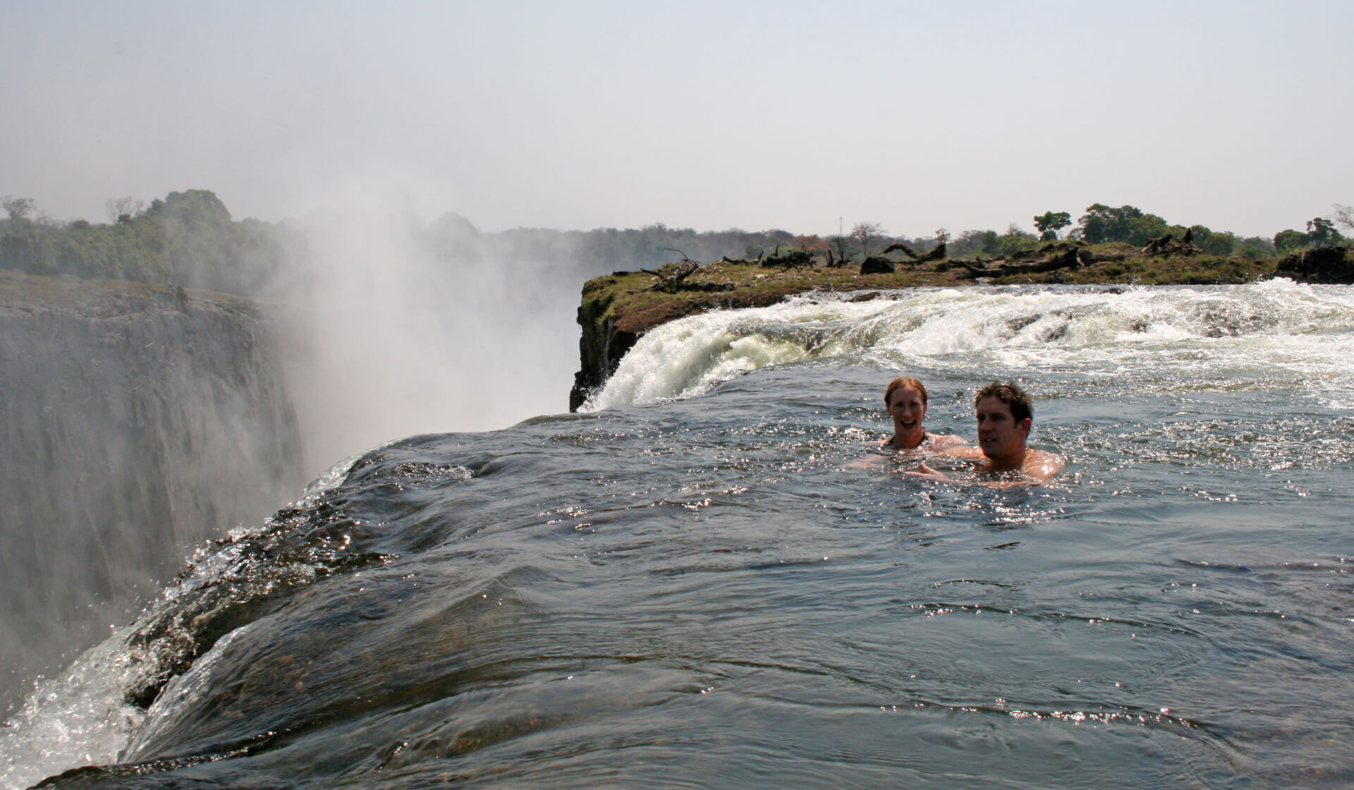 "Couple inside ""Devil's Pool"" on top of Victoria Falls waterfall in Zambia"