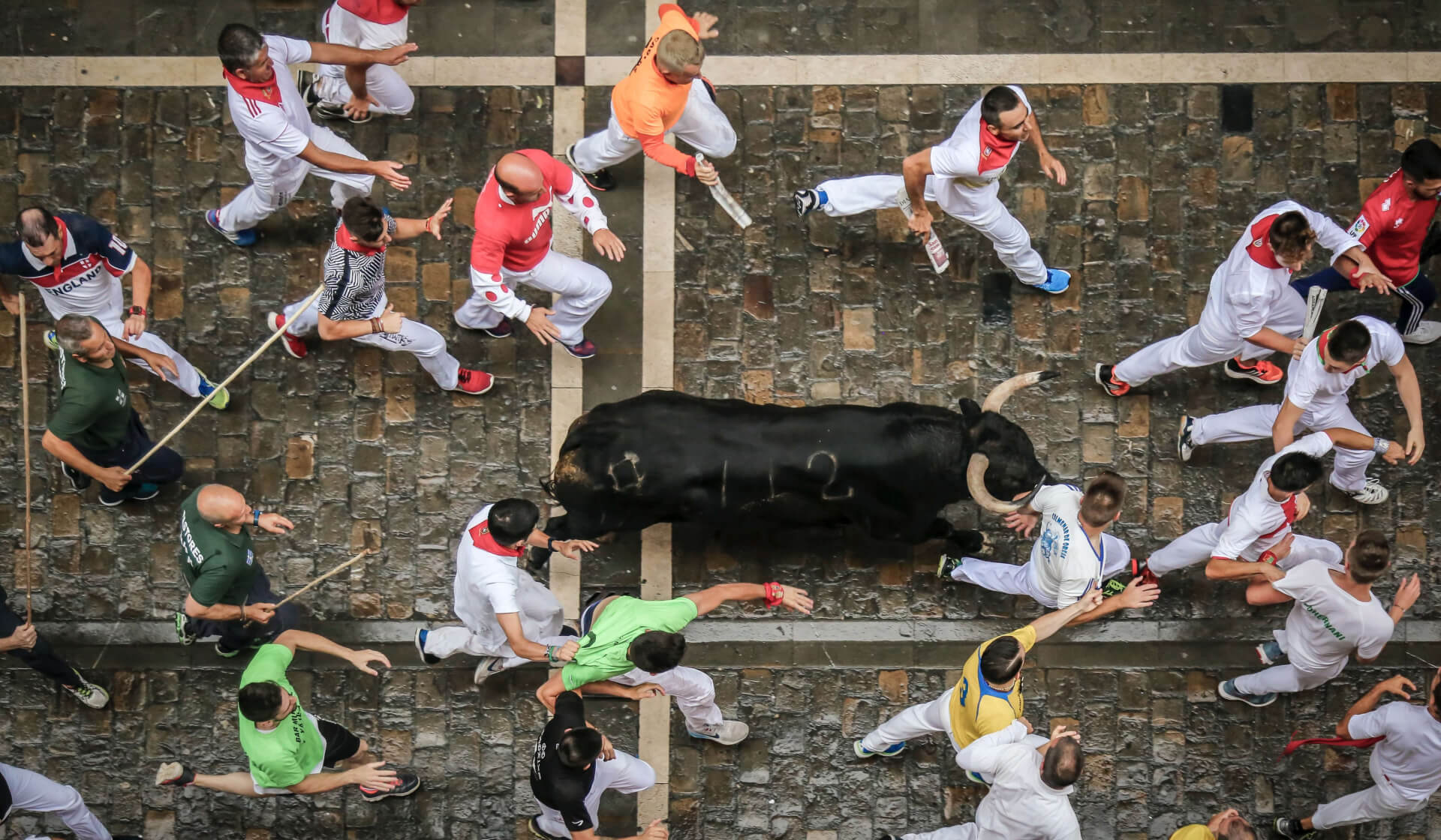 Aerial view of men dressed in red and white running with and being chased by a black bull in Pamplona, Spain