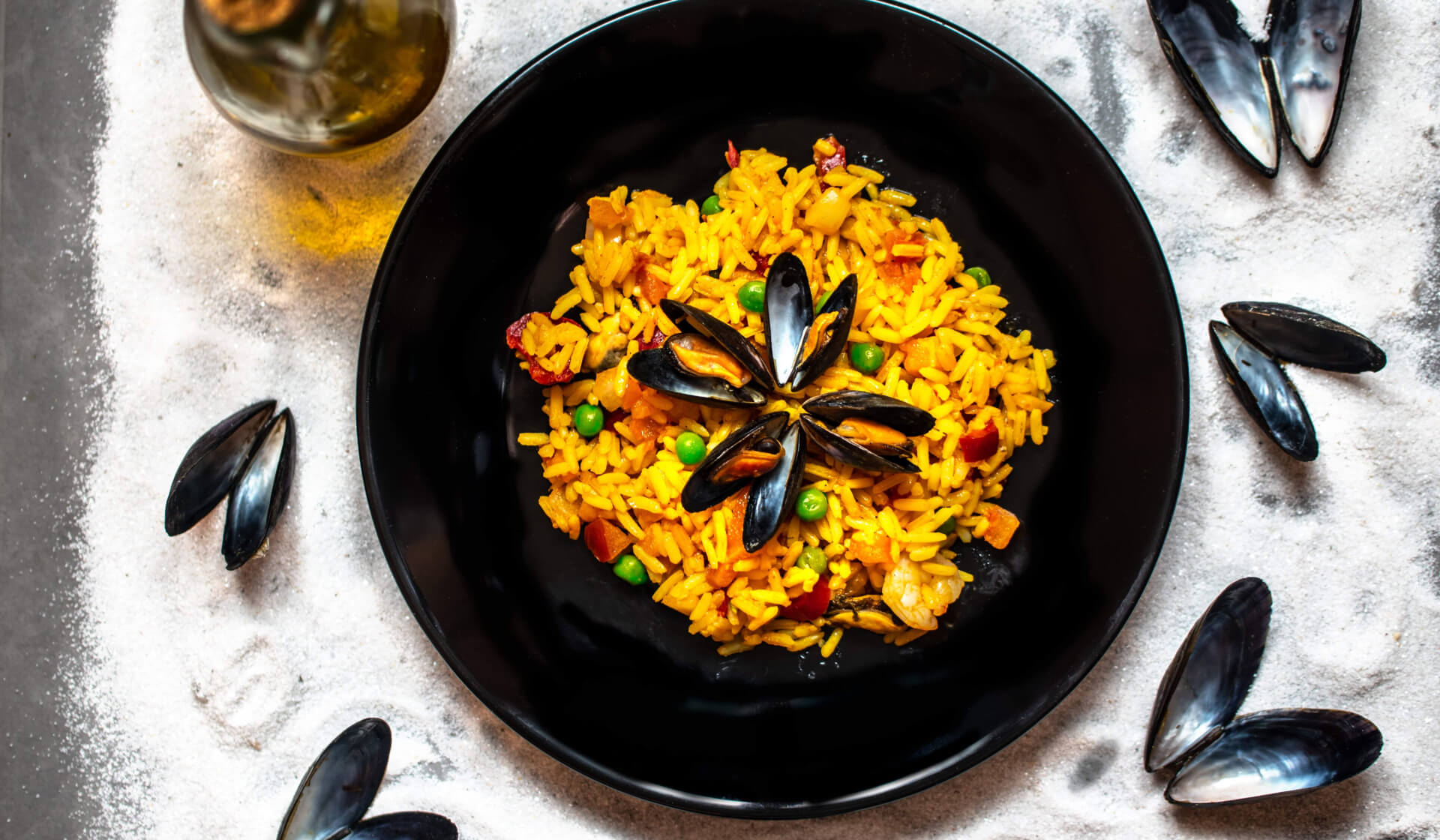 Spanish paella from above with yellow rice, green peas, and clams in a black bowl