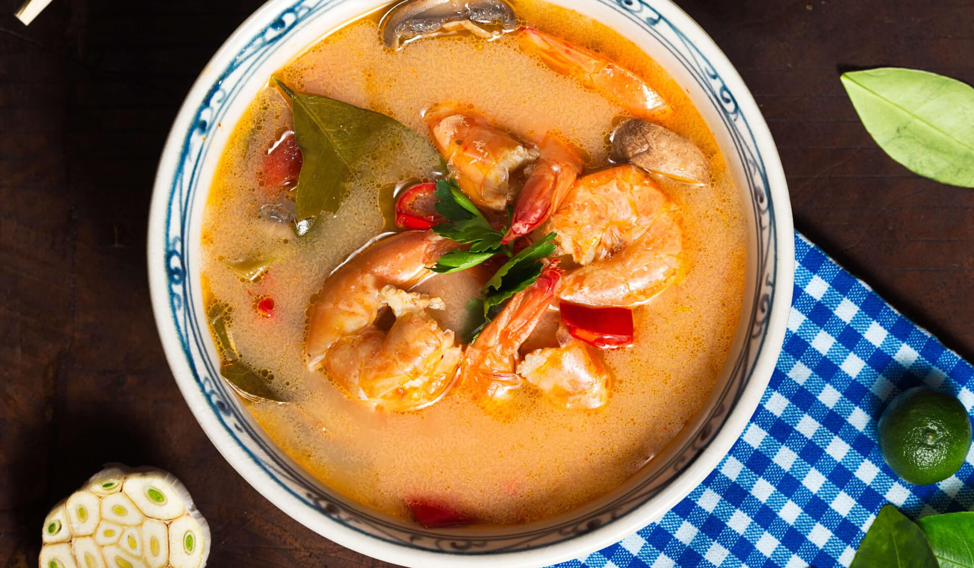 Thai tom yum soup with a redish broth, shrimp, mushrooms, Thai basil, and parsley