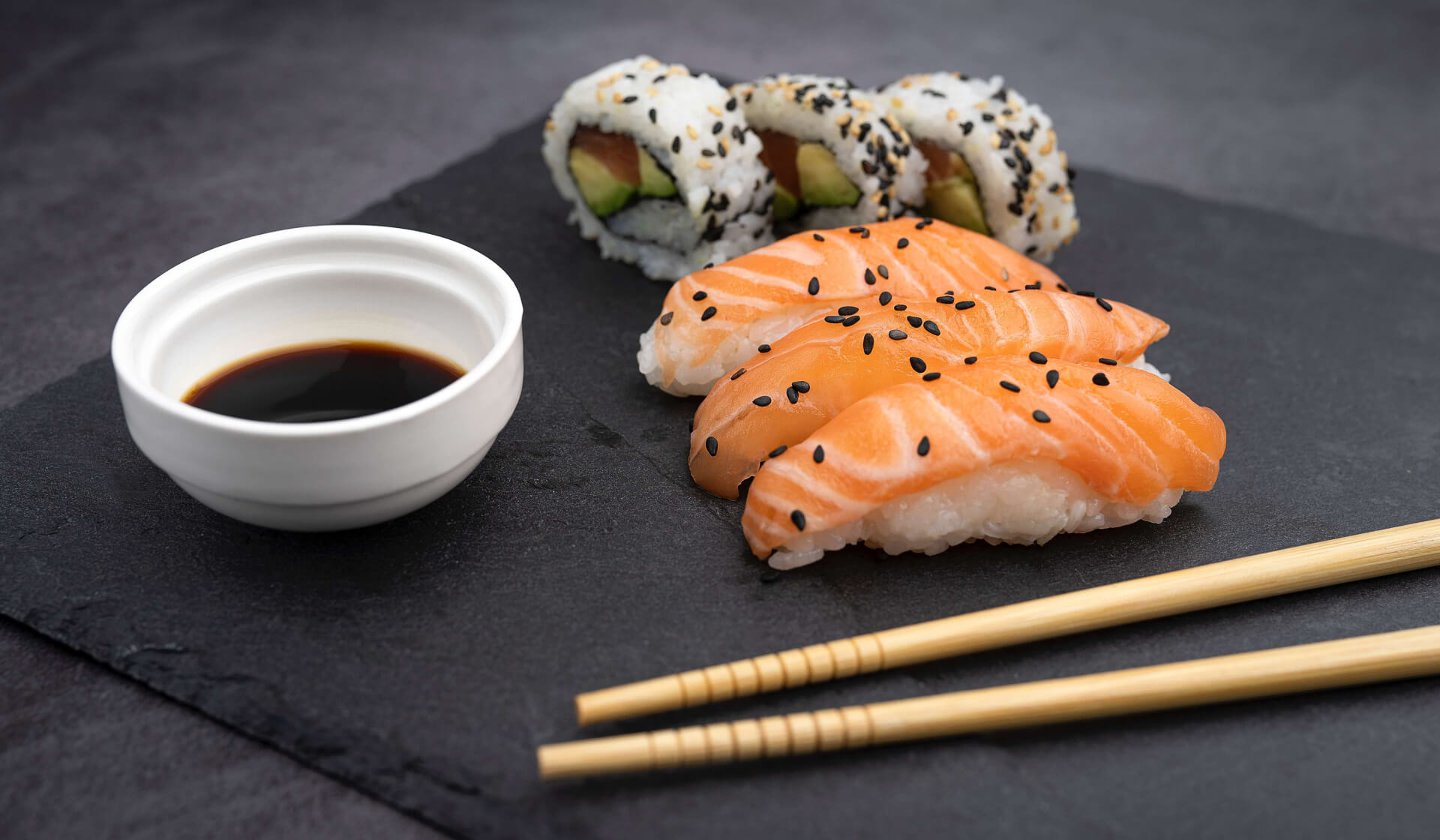 Japanese salmon sushi and a tuna avocado roll on a slate with soy sauce and chopsticks