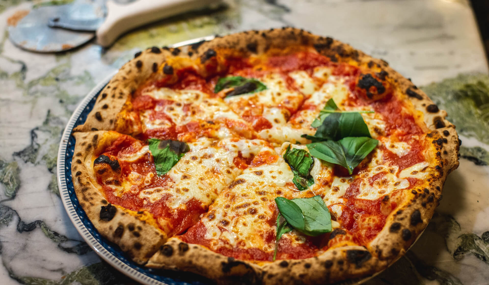 True Italian-style pizza with bubbly crust, lots of melted mozzarella, and fresh basil leaves