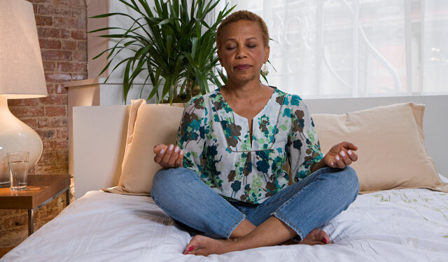 Woman meditating cross-legged on a bed with her eyes closed and her palms in her lap facing up