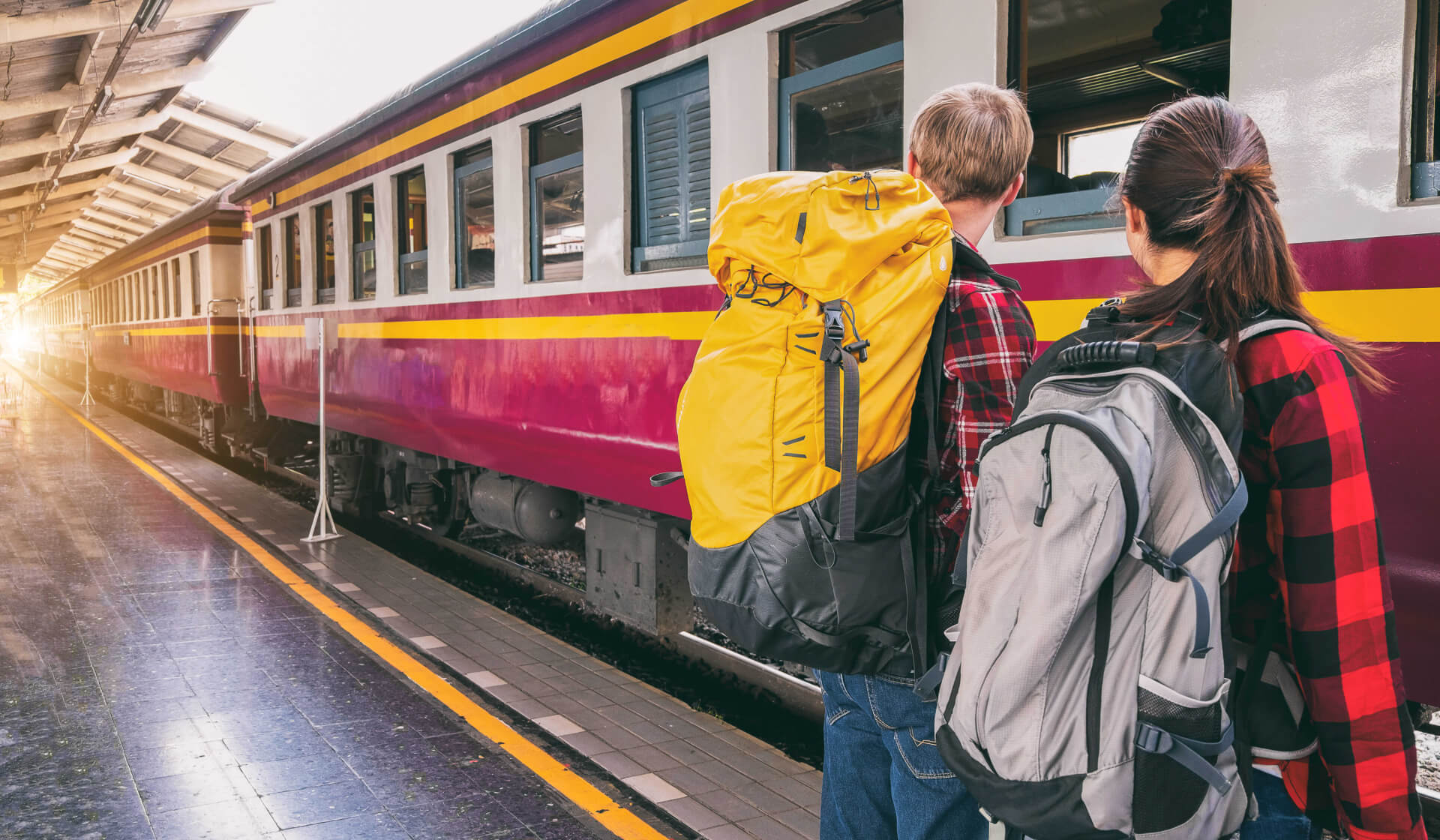 Backpacking couple with yellow and gray backpacks at a train station waiting standing in front of a train pulling in