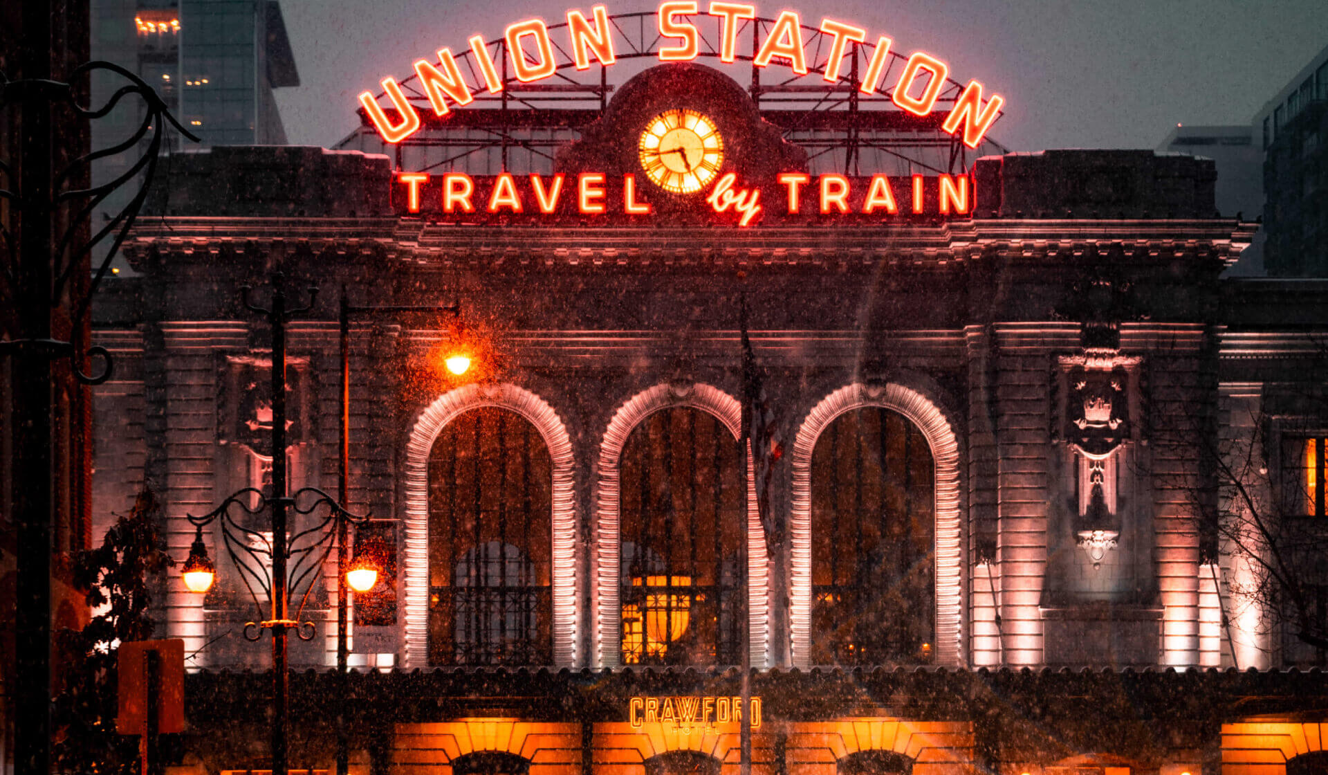 "Union Station train station facade in the snow with neon lights that say ""travel by train"""