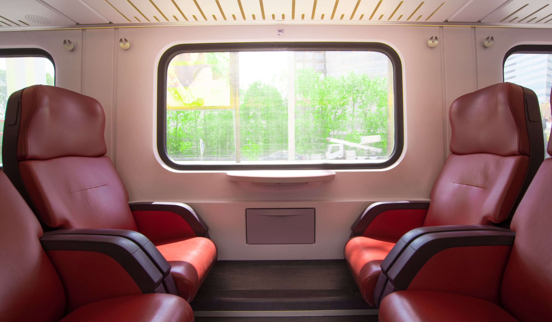 Four large, empty, red leather seats facing each other on a train