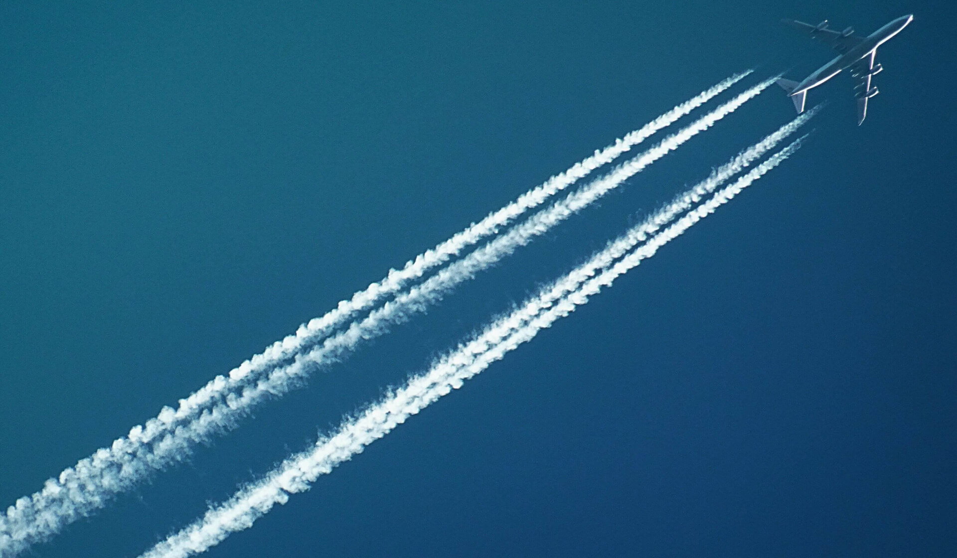 Plane in a clear blue sky with a long trail of smoky emissions behind it