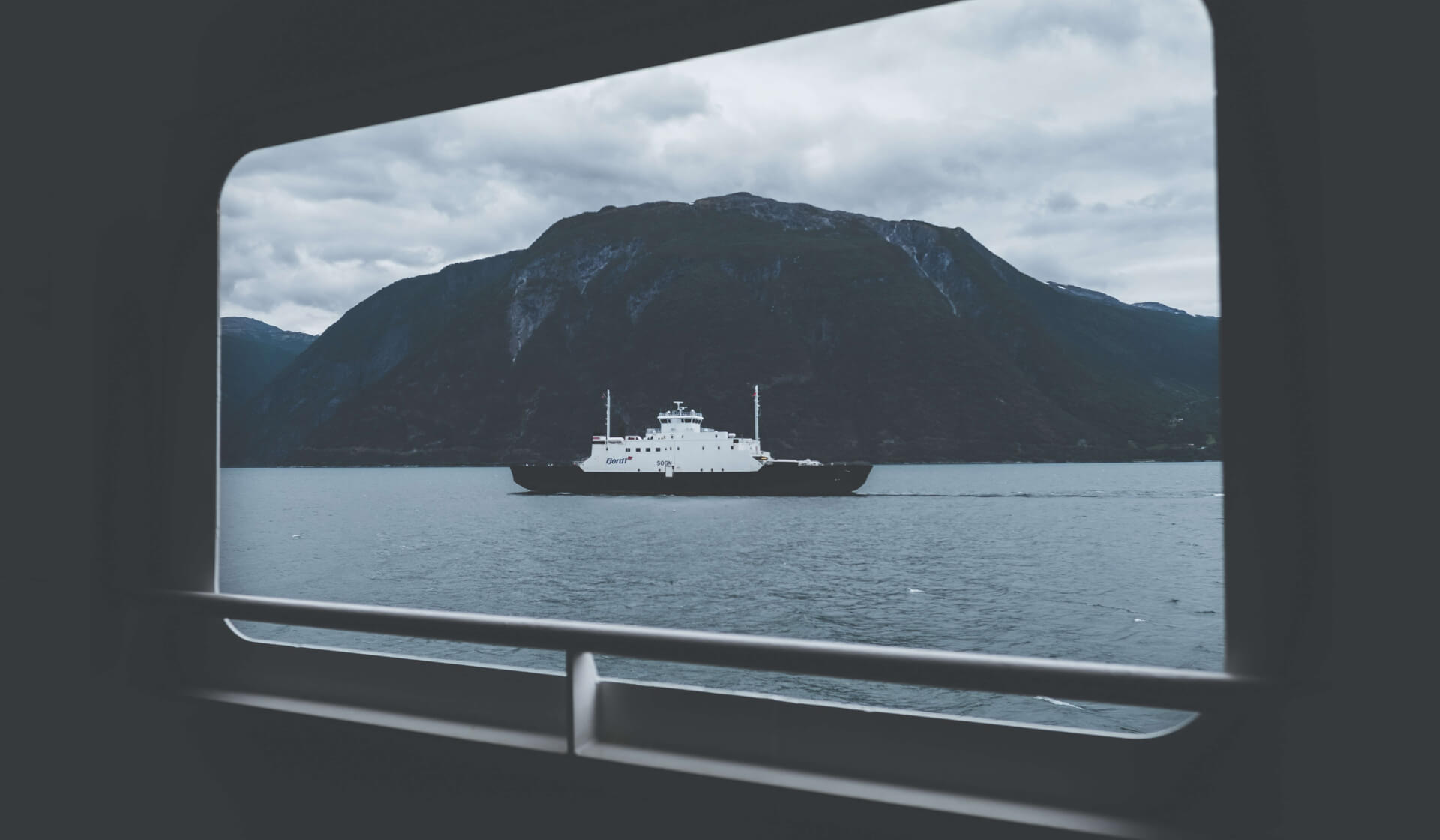 View from a window of a boat passing in front of a mountain over a lake