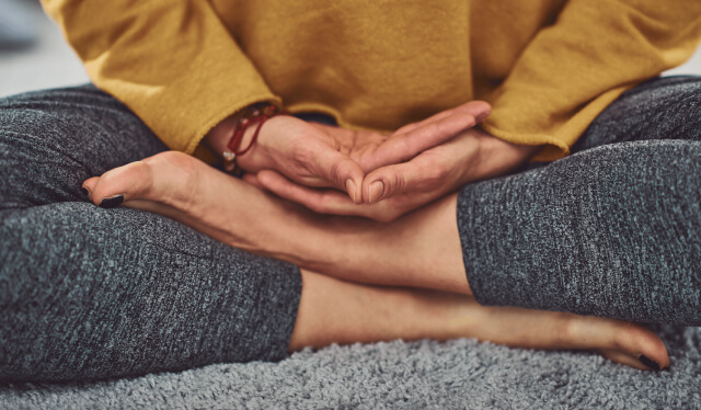 Close-up of a woman's legs as she is sitting meditating cross-legged with her hands in her lap