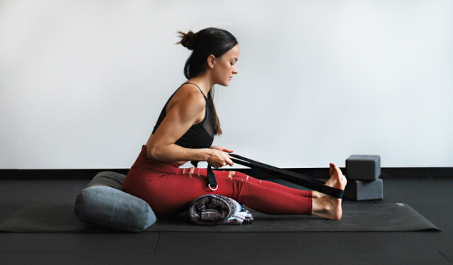 Woman in red leggings sitting on yoga props and folding forward into a yoga pose while holding a yoga strap