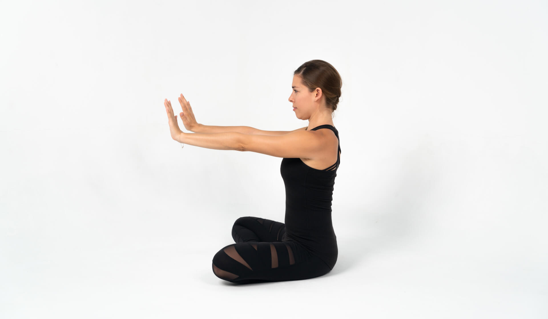 Yoga teacher dressed in all black seated with her arms stretched in front of her against a white backdrop