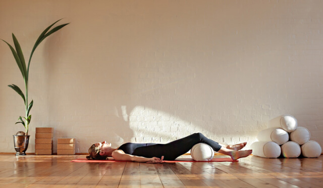 Woman dressed in black laying on the floor with a yoga bolster under her knees practicing Yoga Nidra