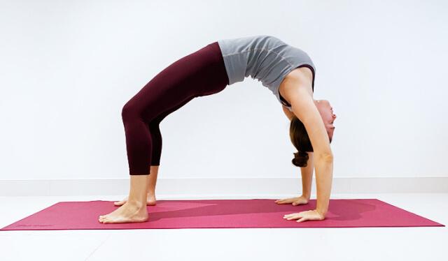 Female yoga teacher practicing a backbend - wheel pose (urdhva dhanurasana) - on a red yoga mat against a white wall