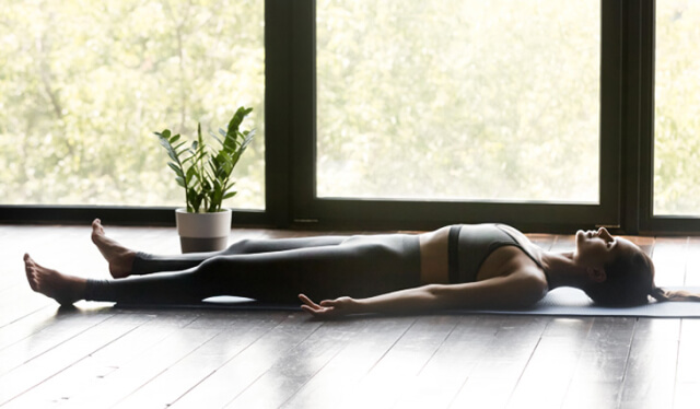 Woman lying down on a yoga mat in front of a plant and window practicing Yoga Nidra