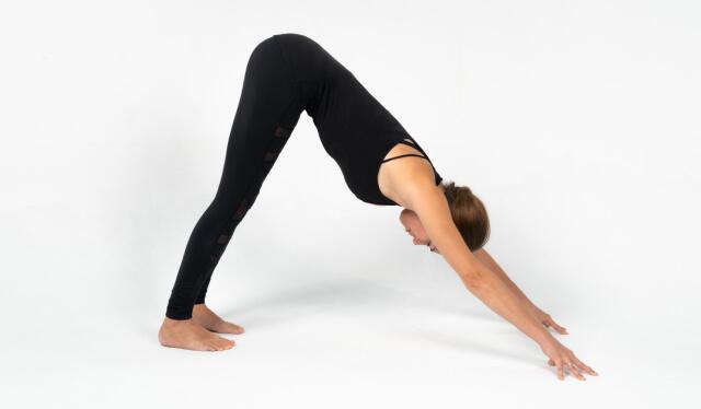 Yoga teacher in all black against a white background practicing downward facing dog (adho mukha svanasana)