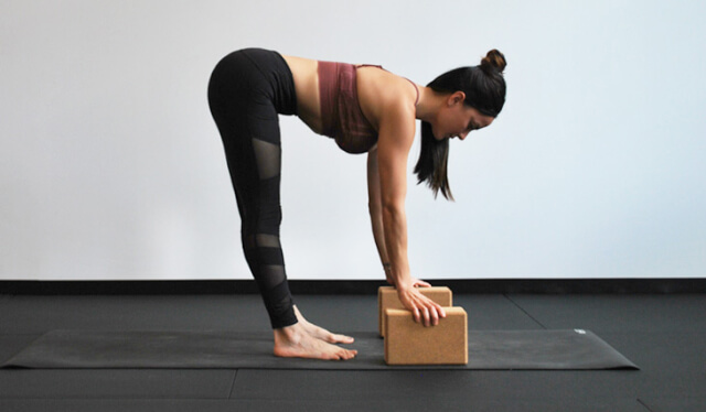 Woman practicing yoga and folding forward to rest her hands onto yoga blocks against a white wall