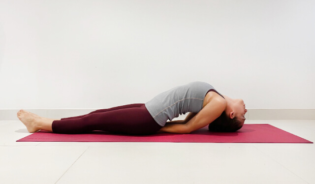 Woman practicing fish pose (matsyasana) lying down on her back with her chest lifted on a pink yoga mat in front of a white wall