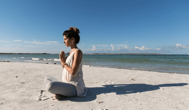 Woman sitting in meditation in the sand on a beach with her eyes closed and her hands in front of her heart