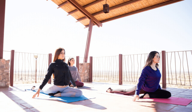 Three women practicing pigeon pose on yoga mats on a balcony overlooking fields