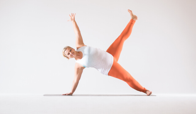Woman yoga teacher with a white shirt and orange leggings against a white background practicing a variation of side plank (vasisthasana)