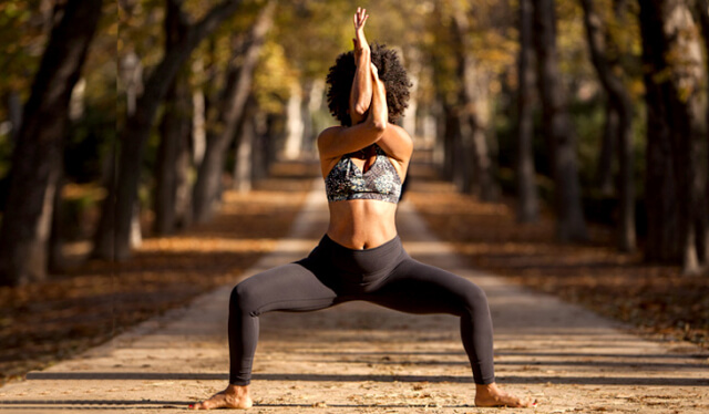 Woman in black leggings and a sports bra practicing goddess pose with eagle arms on a dirt road lined with trees