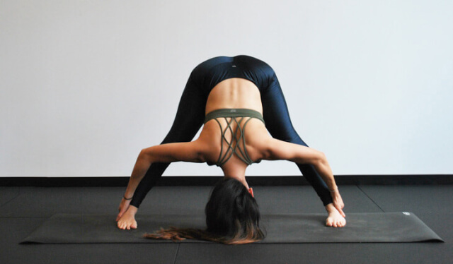 Woman in sports bra and black leggings practicing a wide-legged forward fold in front of a white wall