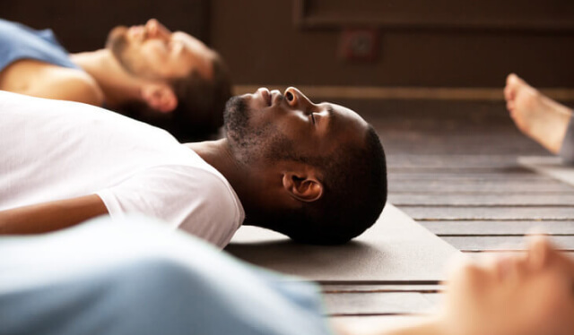 Yoga students lying down on their yoga mats in savasana (corpse pose) with their eyes closed