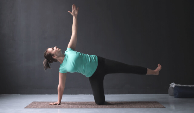 Woman wearing a green shirt and black leggings practicing yoga on a brown mat against a gray wall balancing in a side plank variation