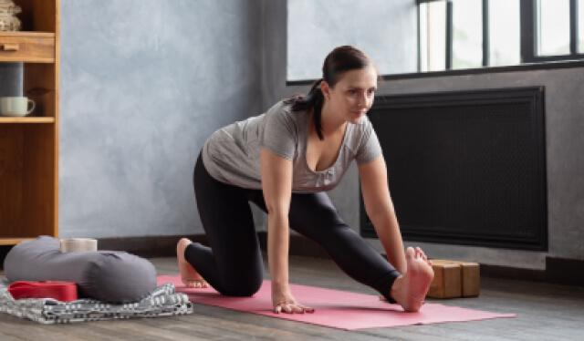 Yoga teacher wearing black yoga pants and a gray shirt practicing a stretch in half splits (ardha hanumanasana) on a pink yoga mat