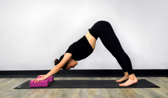 Yoga teacher wearing black leggings and a black shirt practicing downward facing dog with pink yoga blocks under her hands on a black yoga mat against a white wall