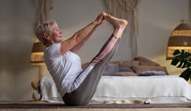Elderly woman practicing the yoga pose navasana (boat pose) in front of a bed