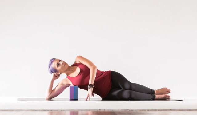 Woman in red shirt and black yoga pants practicing myofascial release by laying on her side with her armpit resting on a yoga block against a white backdrop