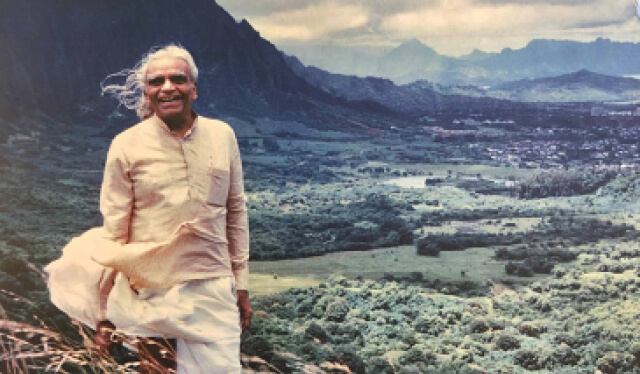 Yoga master teacher BKS Iyengar with his hair blowing in the wind in front of a vast landscape of forest and mountains
