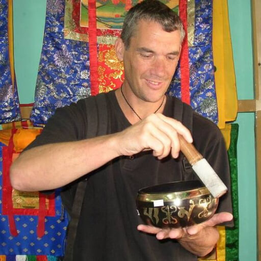 Man in a black shirt playing a Tibetan singing bowl
