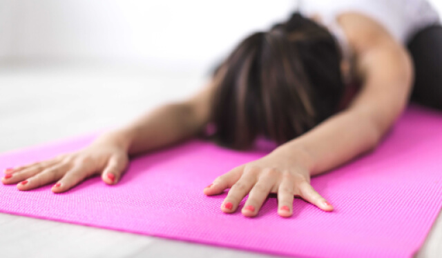 Woman relaxing in child's pose (balasana) on a pink yoga mat