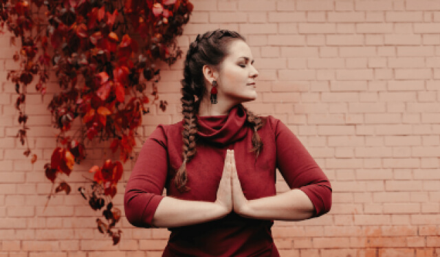 Woman with her hands in prayer at her heart, looking over her left shoulder in a red dress in front of a brick wall